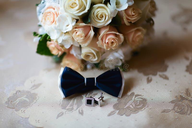 De toebehorencufflinks van het mensen` s huwelijk, en een donkerblauwe vlinder, een band, bruidegomochtend, huwelijksboeket met w stock afbeeldingen