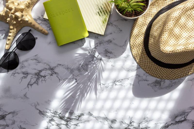 De de toebehorenvlakte van de de zomerreis legt op marmeren achtergrond Paspoort, hoed, zonnebril en zeester voor de zomervakanti royalty-vrije stock fotografie