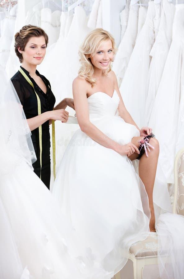 De toekomstige bruid zet de kouseband stock afbeeldingen