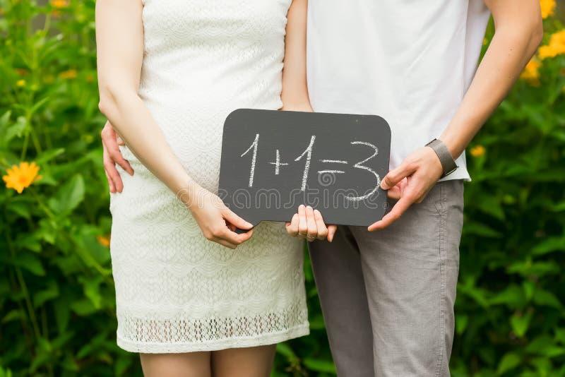 De toekomstige ouders zijn in het tuinclose-up Mens die zwangere vrouw koesteren royalty-vrije stock afbeeldingen