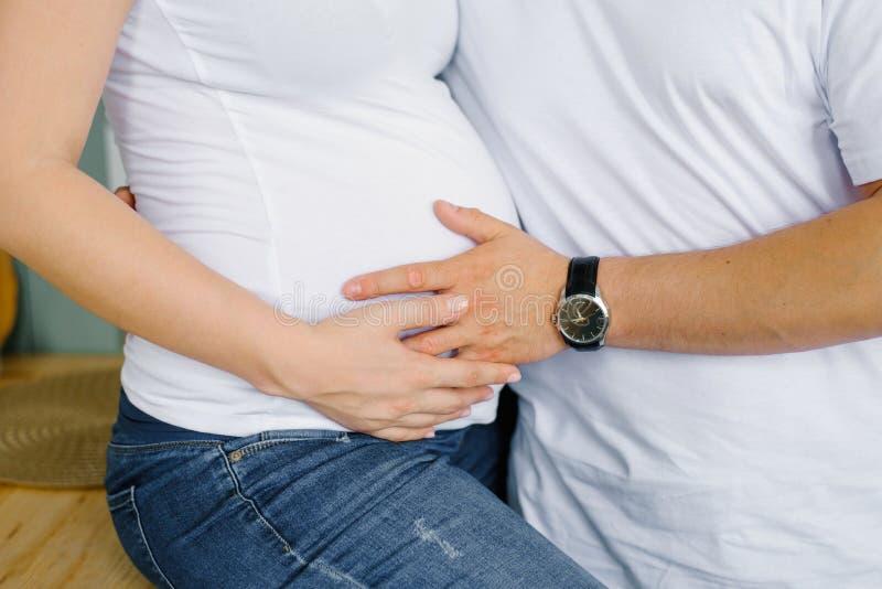 De toekomstige vader houdt zijn hand op de maag van de toekomstige moeder, zijn zwangere vrouw Verwachte ouders wachten royalty-vrije stock foto
