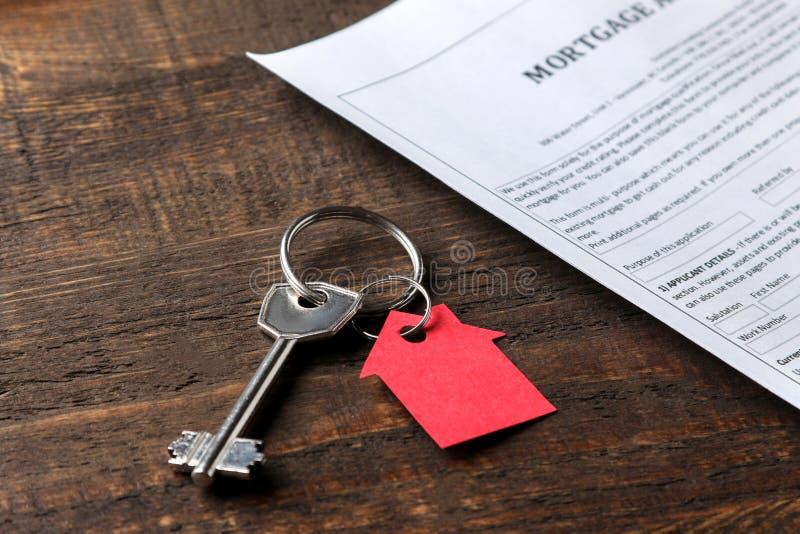 De toepassing van de hypotheek Sleutel met rood keychainhuis en spatie op een bruine houten lijst Concept het kopen van een huis stock foto