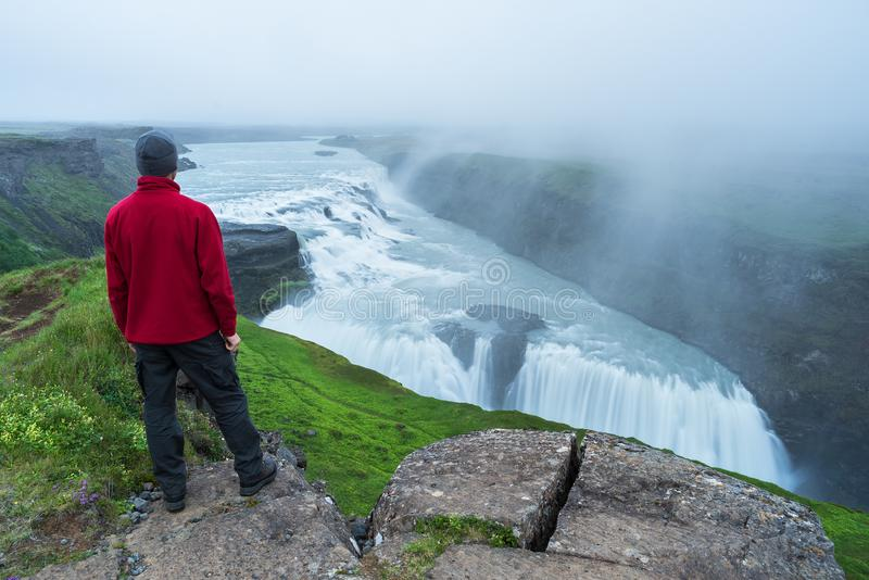 De toerist bekijkt de Gullfoss-waterval in IJsland stock afbeelding