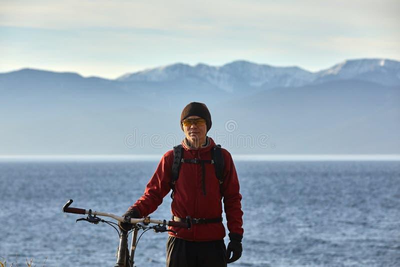 De toerist berijdt een fiets met brede wielen langs de kust van Meer Baikal royalty-vrije stock foto's