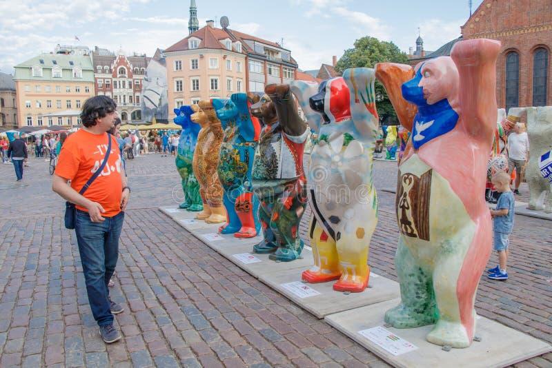 De toerist die de kleurrijke beren bij de internationale kunsttentoonstelling bekijken verenigde Buddy Bears De beercirkel was stock fotografie