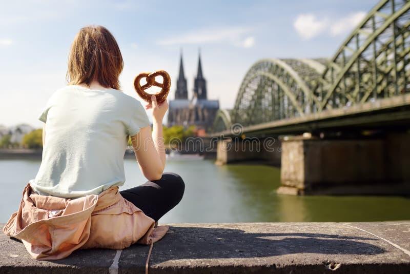 De toerist eet traditionele pretzelzitting op dijk van Rijn op achtergrond van de Kathedraal van Keulen en Hohenzollern-Brug in K stock fotografie