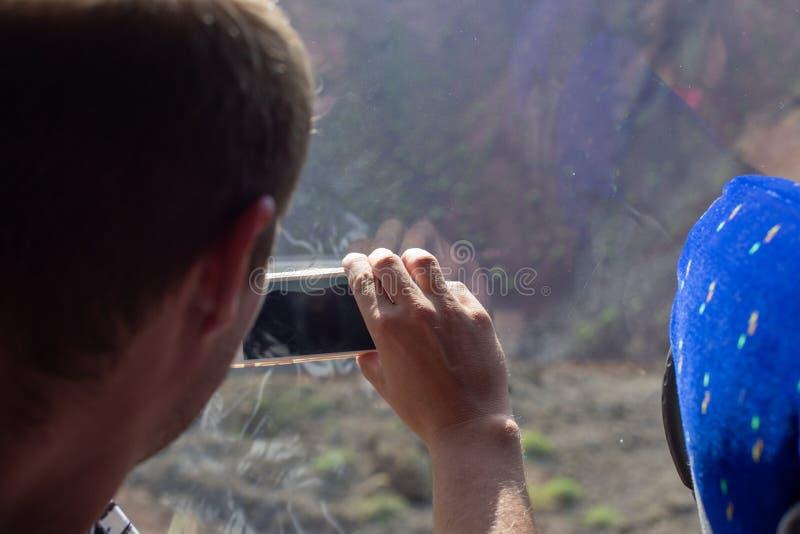 De toerist fotografeert het landschap door het venster van een toeristenbus stock foto's