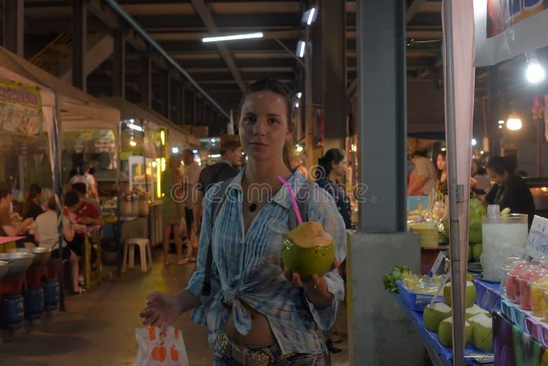 De toerist koopt kokosnoot bij de markt van de nachtkruidenierswinkel royalty-vrije stock fotografie