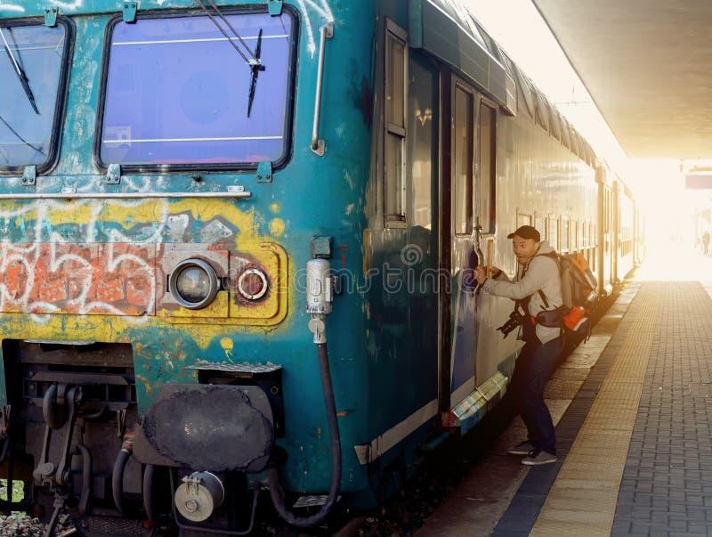 De toerist met een rugzak krijgt op de trein stock foto