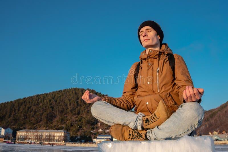 De toerist met een rugzak mediteert zitting in Lotus-positie inzake het ijs van meer Baikal stock afbeeldingen