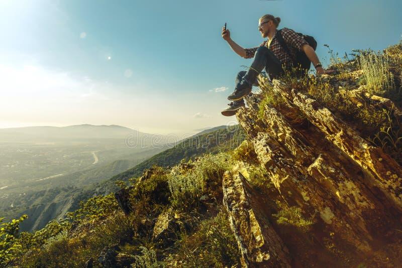 De toerist met rugzak zit bovenop de berg en neemt beelden van het landschap op cellphone stock foto