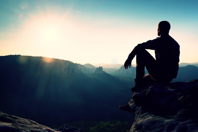 De toerist neemt een rust Knappe jonge mensenzitting op de rots en het genieten van van mening in nevelige rotsachtige bergen stock afbeeldingen