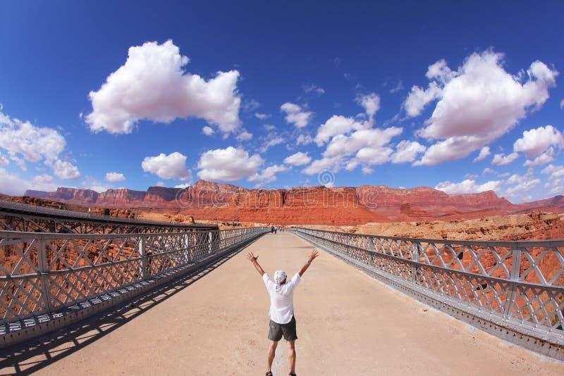 De toerist stemt in met zonnemiddag over de brug stock fotografie