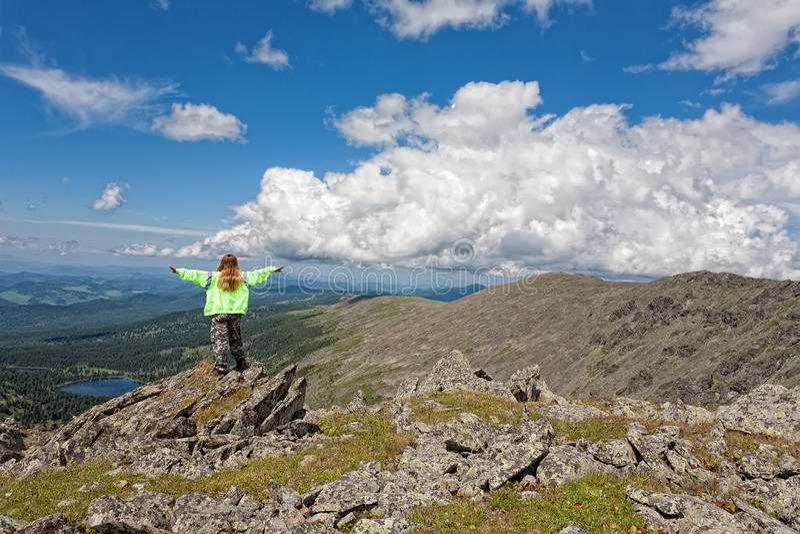 De toerist van het meisje om zich op de rots te bevinden royalty-vrije stock foto