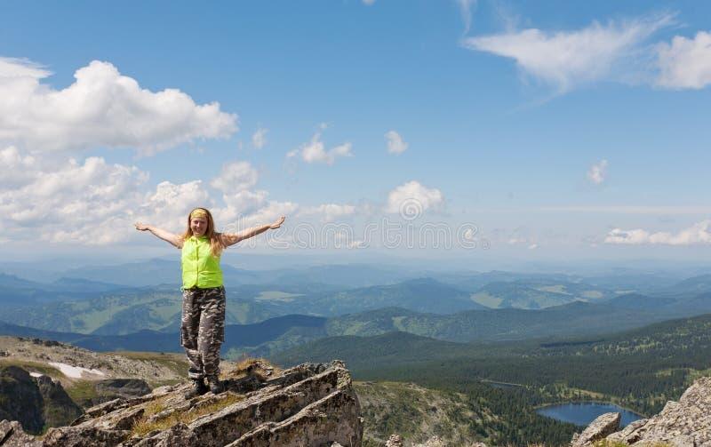 De toerist van het meisje om zich op de rots te bevinden royalty-vrije stock afbeeldingen