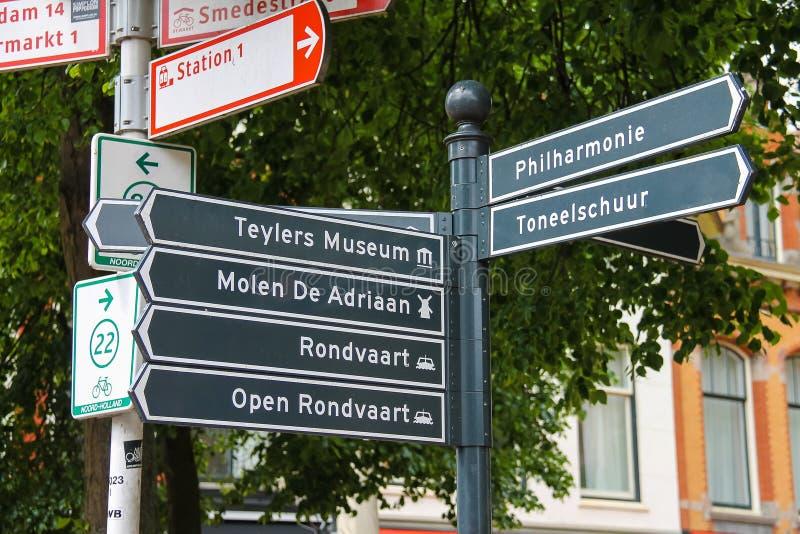 De toerist voorziet bij de kruispunten in het centrum van Haarlem van wegwijzers royalty-vrije stock afbeelding
