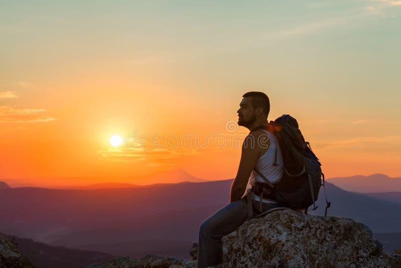De toerist zit in de bergen royalty-vrije stock afbeelding