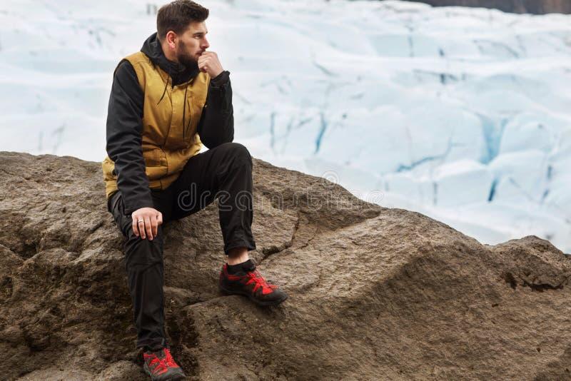 De toerist zit dichtbij de gletsjerijsberg in IJsland stock afbeeldingen