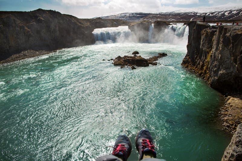 De toerist zit op een klip dichtbij de rivier, die zijn benen hangen neer, v stock fotografie