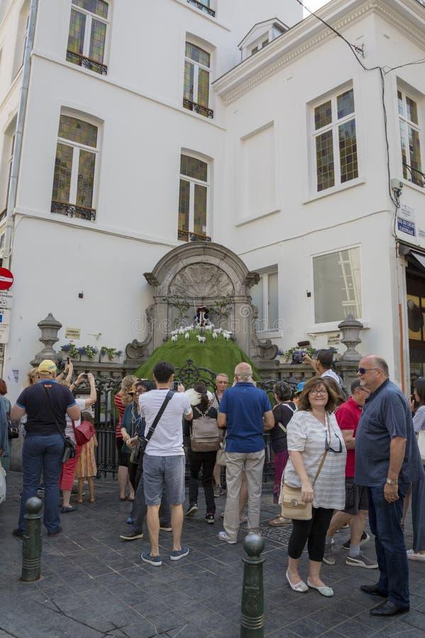 De toeristen bekijken Manneken Pis gekleed als herders` s kostuum stock afbeeldingen
