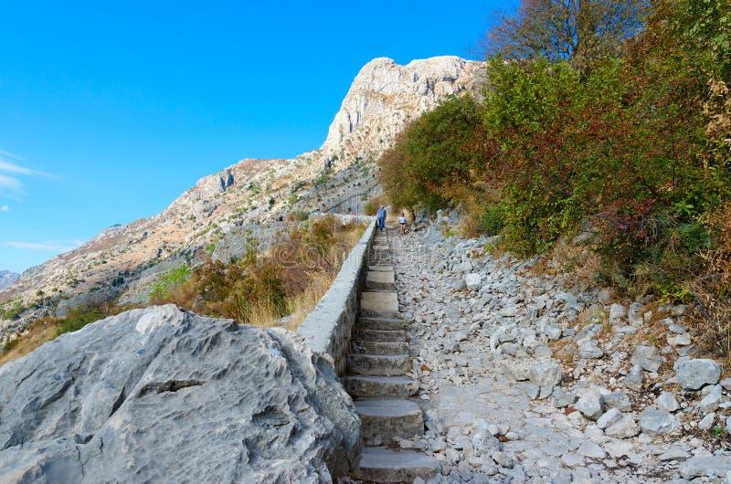 De toeristen beklimmen treden aan ruïnes van oude vesting boven Kotor en Baai van Kotor, Montenegro royalty-vrije stock afbeelding