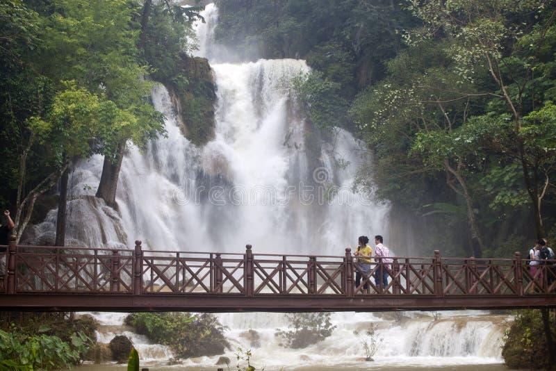 De toeristen bezoeken een waterval royalty-vrije stock afbeeldingen