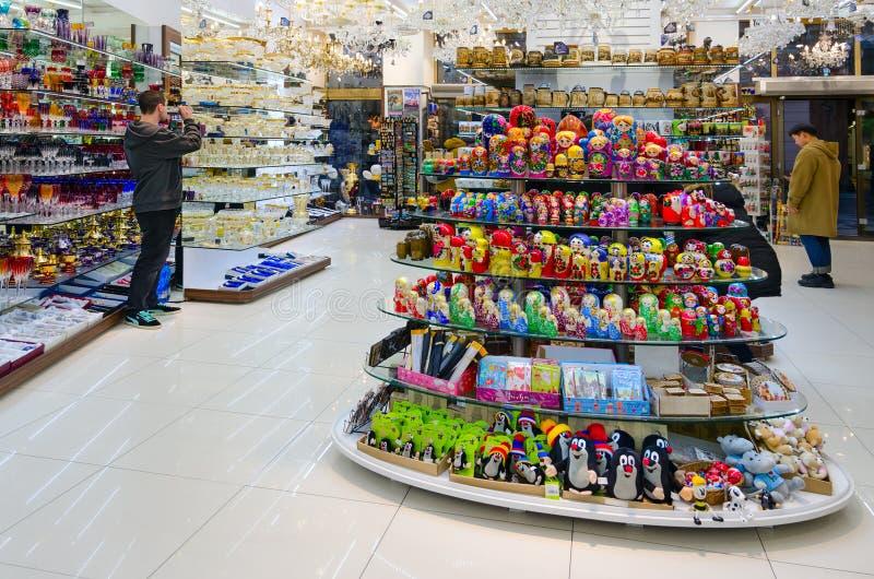 De toeristen bezoeken herinneringswinkel in Praag, Tsjechische Republiek Beroemd Boheems glas op planken in giftopslag royalty-vrije stock afbeeldingen