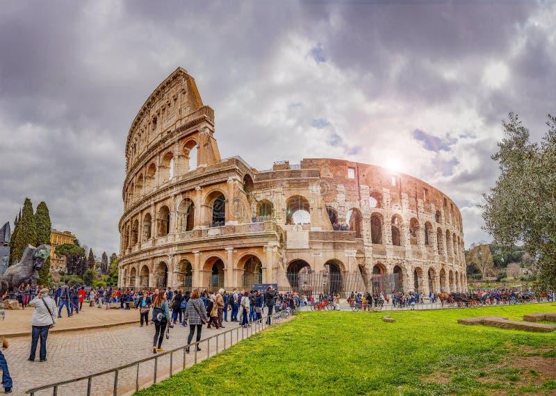 De toeristen die onder colosseum in Rome op een bewolkte dag lopen weten stock afbeeldingen