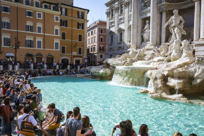 De toeristen die van een heldere zonnige dag in Rome genieten die de beroemde Trevi fontein bezoeken monumen stock foto