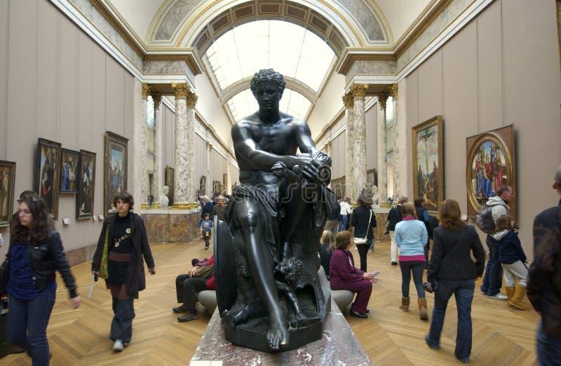 De toeristen die van het Louvre beeldhouwwerk bezoeken stock afbeeldingen