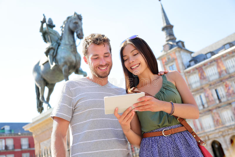 De toeristen die van Madrid tabletreis app gebruiken stock foto's