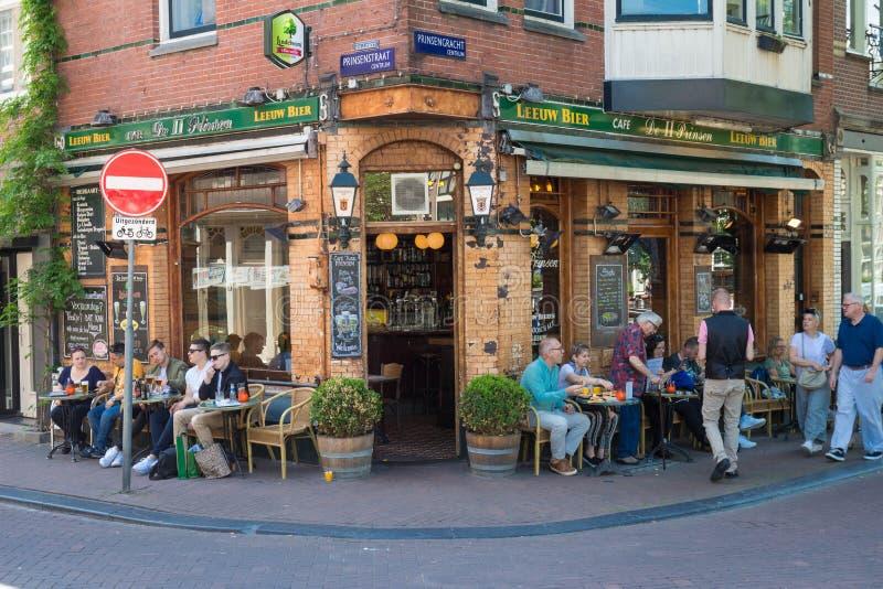 De toeristen en de plaatselijke bevolking genieten van Nederlandse die bar II Prinsen in het centrum van Amsterdam, Nederland wor stock afbeeldingen