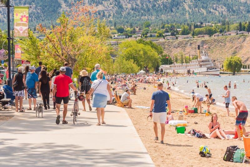 De toeristen en de plaatselijke bewoners genieten van het strand en de gang op een de zomermiddag stock foto's