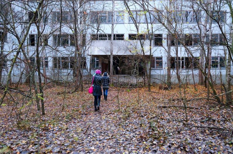 De toeristen gaan naar de verlaten schoolbouw in dode spookstad van Pripyat in NPP van Tchernobyl vervreemdingsstreek, de Oekraïn royalty-vrije stock afbeelding