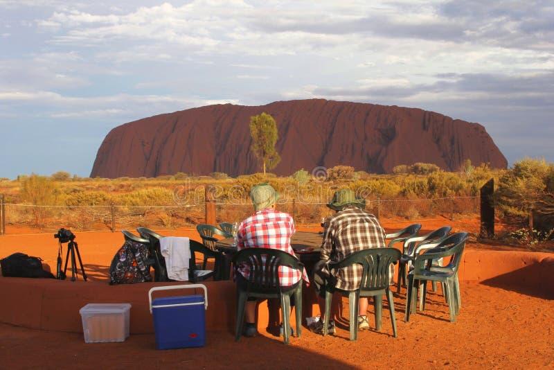 De toeristen genieten van de zonsondergang bij Ayers-Rots stock fotografie