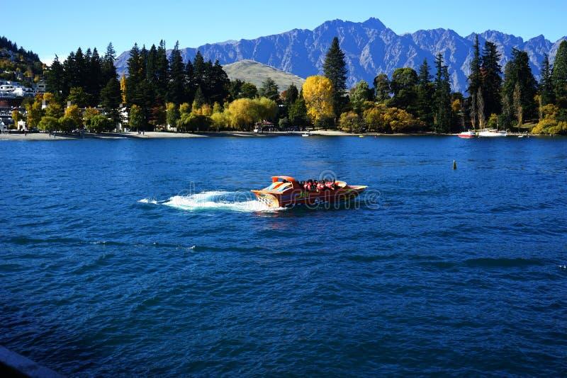 De toeristen genieten van een rit van de hoge snelheids straalboot op de Shotover-Rivier in Queenstown, Nieuw Zeeland royalty-vrije stock fotografie