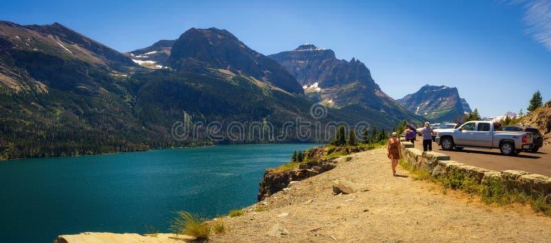 De toeristen genieten van de mening van Heilige Mary Lake in Gletsjer Nationaal Park stock foto