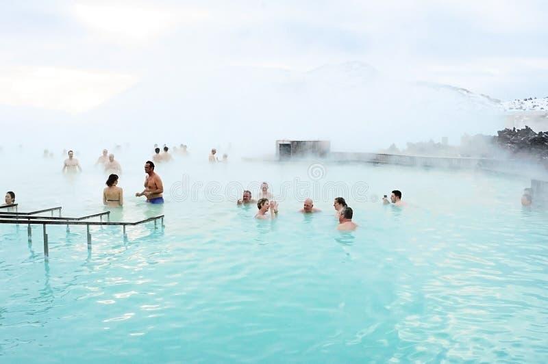 De toeristen genieten van nemend een bad bij Blauwe Lagune, IJsland royalty-vrije stock foto's