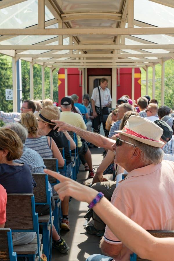 De toeristen genieten van reizend in het open panoramavervoer van Chur naar Arosa en punt bij de gezichten royalty-vrije stock afbeelding