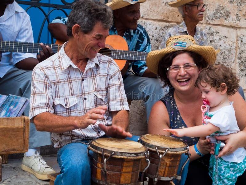 De toeristen in Havana, het mamma en weinig dochter spelen met straatmusici, Cuba stock afbeelding