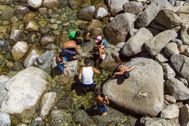De toeristen koelen hun benen in het meer van lagere Yosemite wate royalty-vrije stock afbeelding