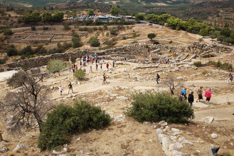 De toeristen lopen door de Leeuw` s Poort van Mycenae-citadel stock afbeeldingen