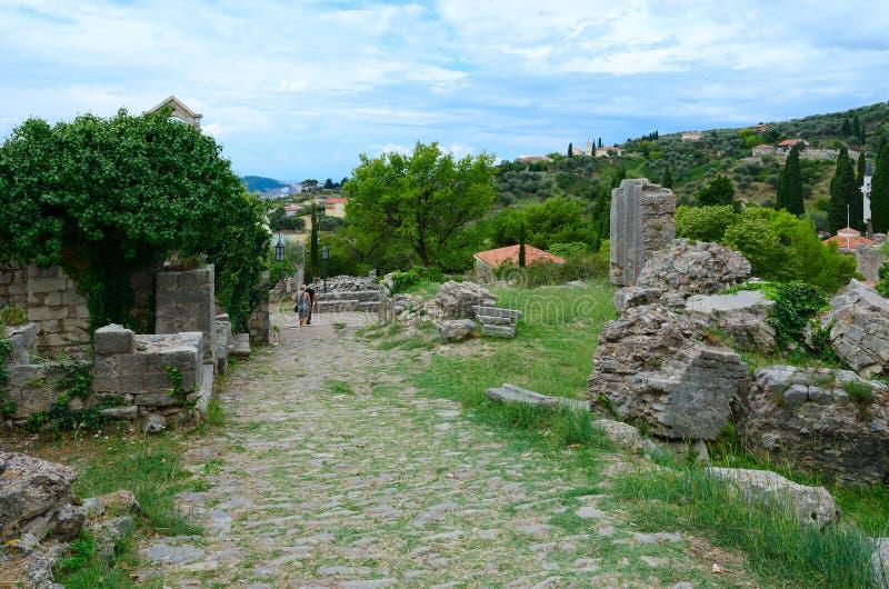 De toeristen lopen langs weg onder ruïnes van oude vesting in Oude Bar, Montenegro stock afbeeldingen