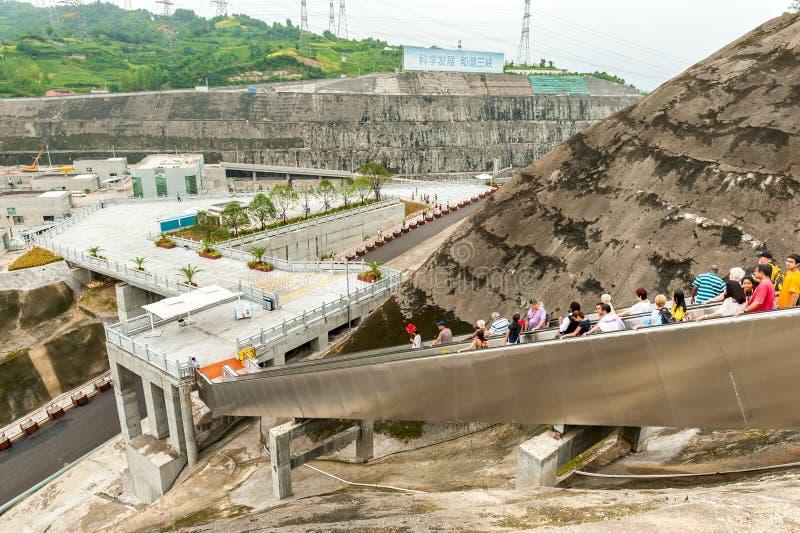 De toeristen lopen onderaan de roltrap met een het bekijken platform stock foto's