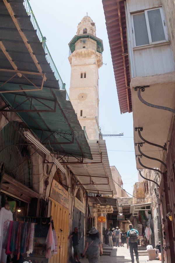 De toeristen lopen onderaan via dolorosastraat in de oude stad van Jeruzalem, Israël royalty-vrije stock fotografie