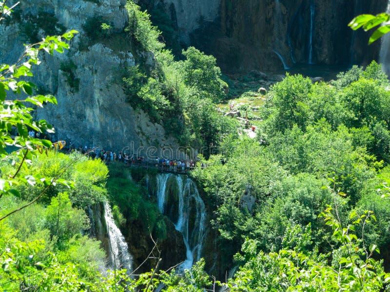 De toeristen lopen op een hangbrug dichtbij de waterval in Plitvice, Kroatië royalty-vrije stock fotografie