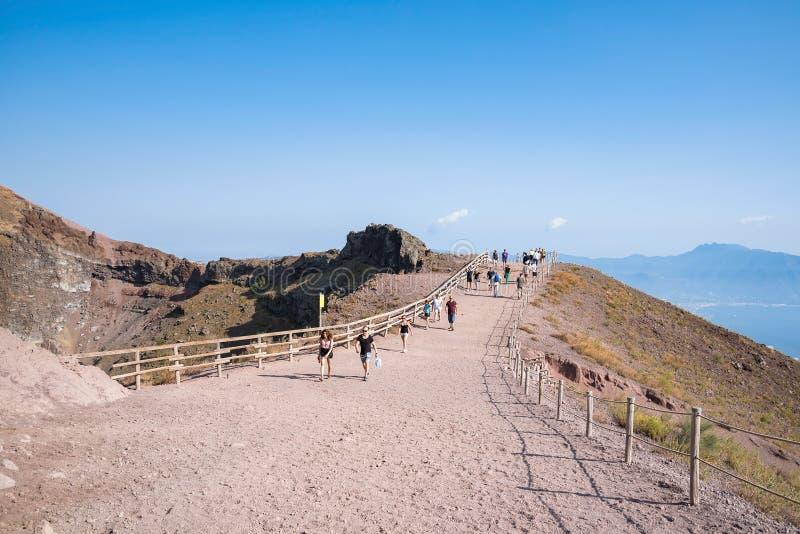 De toeristen lopen rond de krater van de Vesuvius stock foto