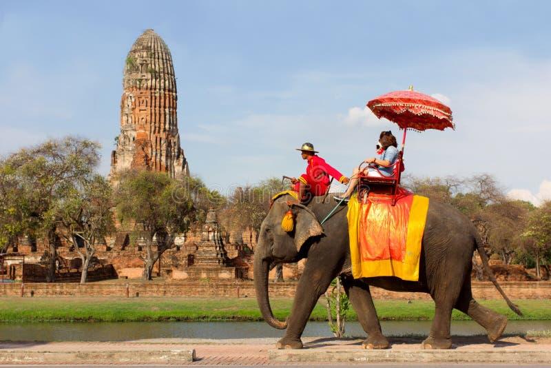 De toeristen nemen een olifantsrit rond historische plaats in Wat Phra Ram, in Ayutthaya, Thailand stock afbeelding