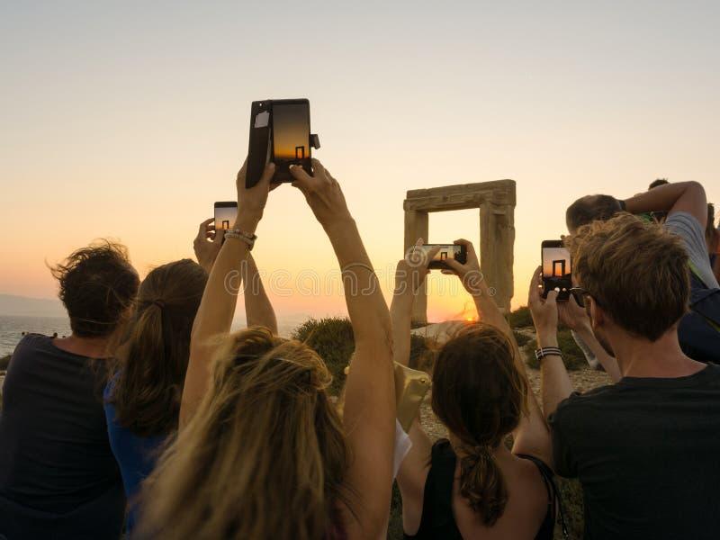 De toeristen nemen foto's van een monument met hun smartphones tijdens de zonsondergang stock foto