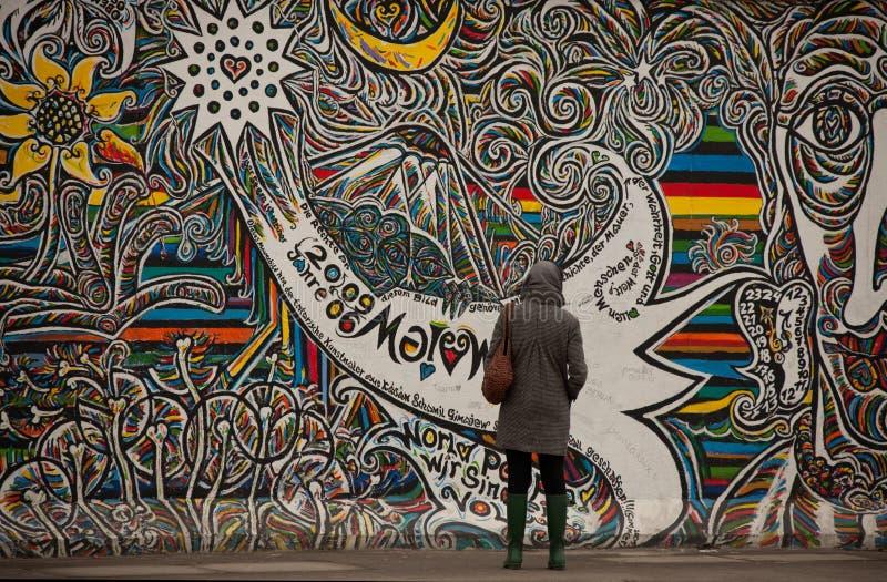 De toeristen onderzoeken graffiti op de muur van Berlijn stock fotografie